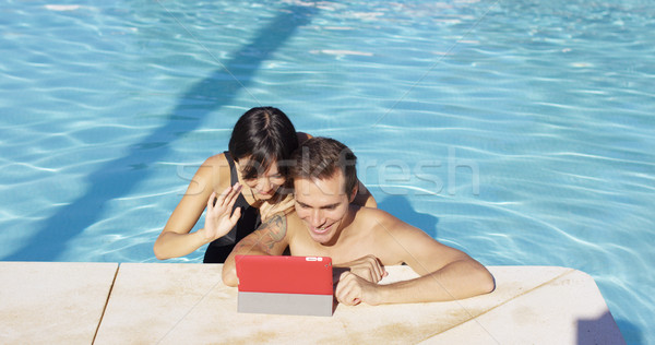 Smiling couple in swimming pool use digital device Stock photo © dash