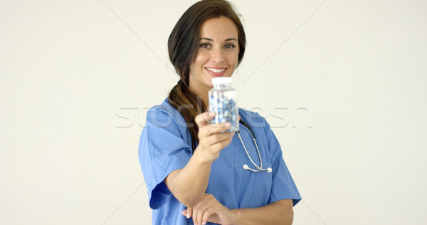 Young brown haired doctor in scrubs holds bottle Stock photo © dash