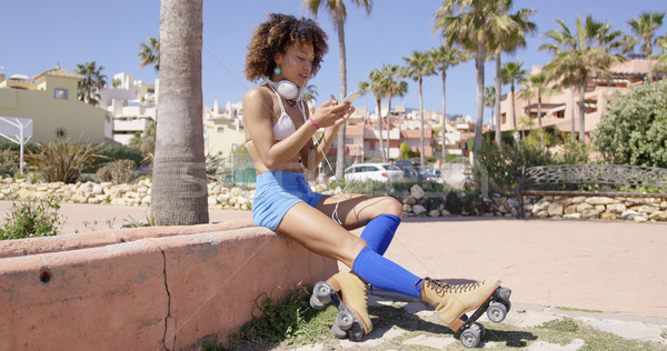 Female wearing rollerskates sitting on curb Stock photo © dash