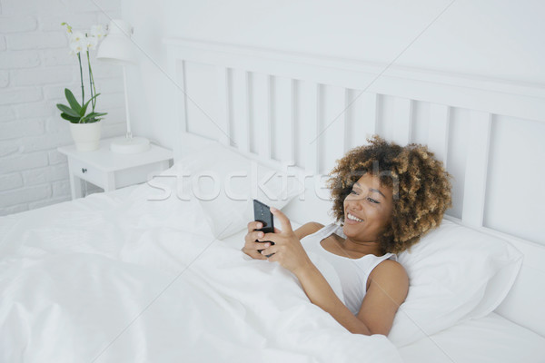 Smiling woman relaxing with phone in bed Stock photo © dash