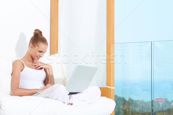 Smiling Woman Chatting on Laptop at Couch Stock photo © dash