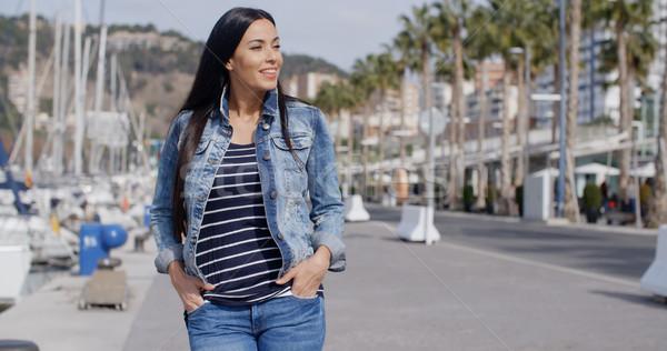 Stock photo: Casual woman enjoying a walk through a marina