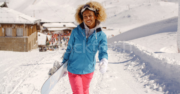 Smiling pretty young woman carrying a snowboard Stock photo © dash