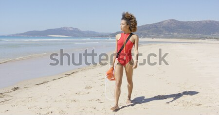 Female lifeguard goes along beach Stock photo © dash