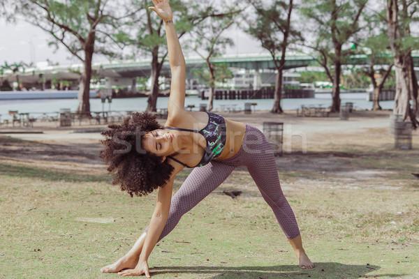 Black sportive girl training asana on lawn Stock photo © dash
