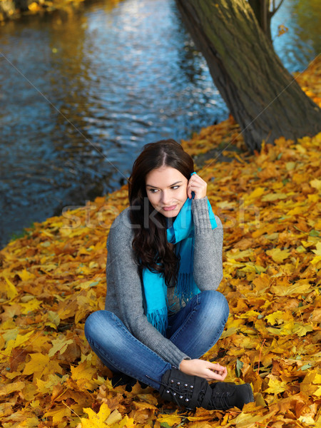 Woman in Autumn Outfit Sitting on Dry Leaves Stock photo © dash
