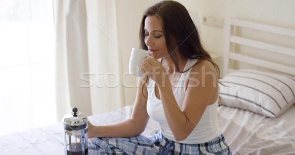 Young woman drinking a mug of fresh coffee Stock photo © dash