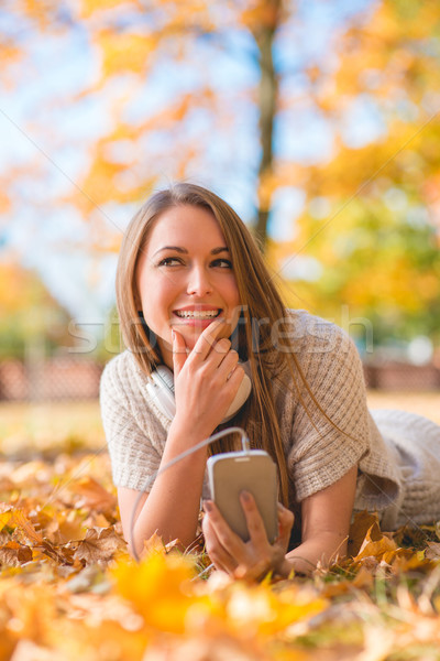 Pretty Lady Lying on Dry Leaves with Phone Stock photo © dash
