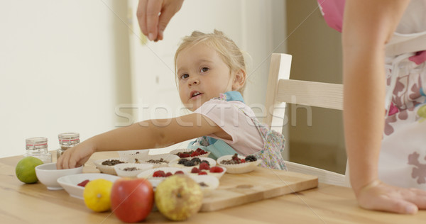 Child watching woman sprinkle candy on muffins Stock photo © dash