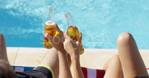 Couple relaxing at the pool with beers Stock photo © dash