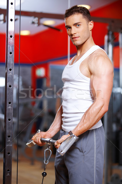 Athletic young man working out in a gym Stock photo © dash