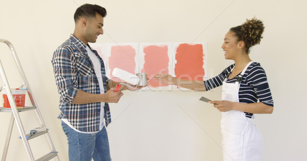 Laughing young couple choosing a paint color Stock photo © dash