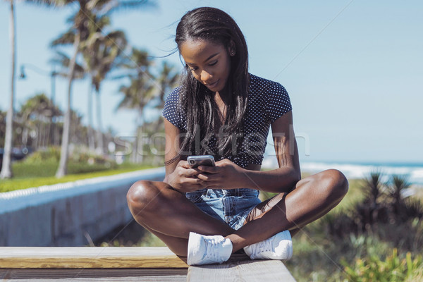 Beautiful woman using phone on fence Stock photo © dash