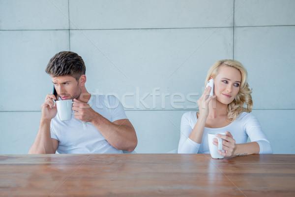 Couple both using their mobile phones Stock photo © dash