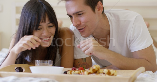 Couple having fruit and waffle breakfast in bed Stock photo © dash