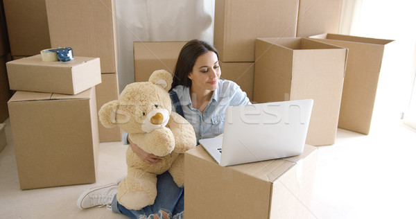 Young woman moving house with her teddy bear Stock photo © dash