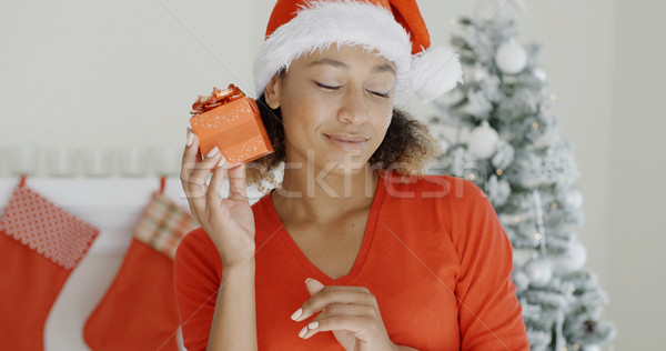 Curious young woman shaking her Christmas gift Stock photo © dash