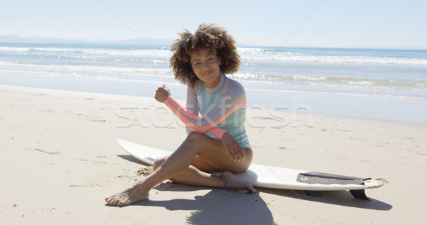Happy female sitting on a surfboard Stock photo © dash