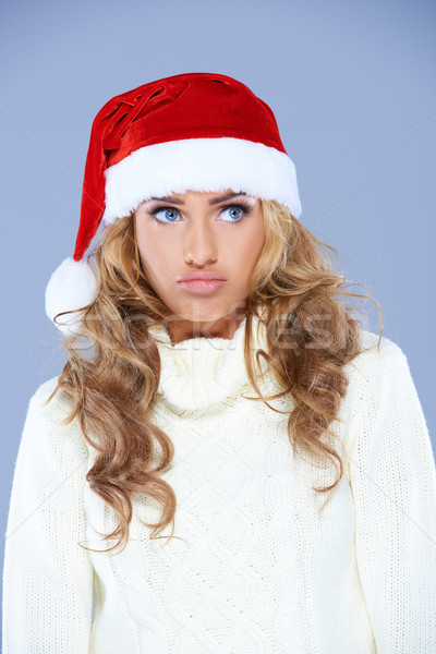 Charismatic young woman wearing a red Santa hat Stock photo © dash