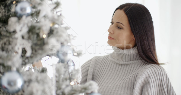 Pretty young woman decorating her Christmas tree Stock photo © dash