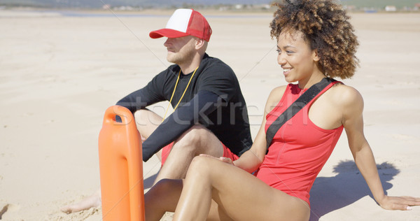 Smiling lifeguards sitting on beach Stock photo © dash