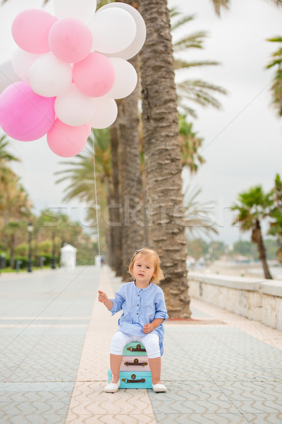Happy little girl holding a bunch of balloons Stock photo © dash