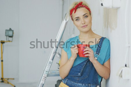 Smiling woman carpenter leaning on wall  Stock photo © dash