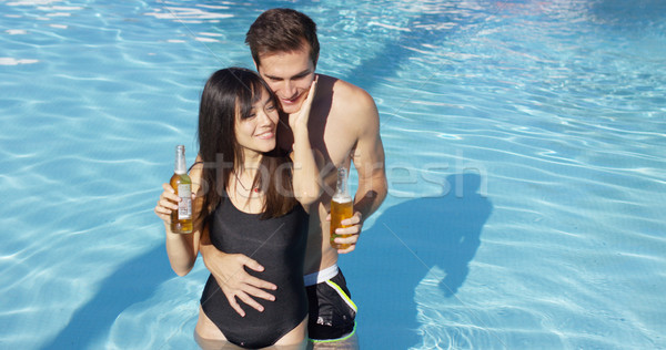 Couple in swimming pool hold frothy drinks Stock photo © dash