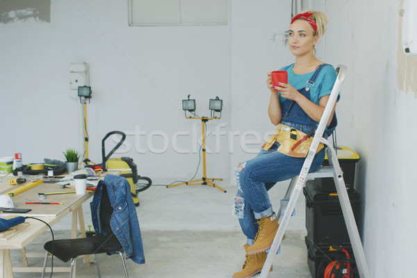 Female carpenter resting on stepladder with beverage  Stock photo © dash
