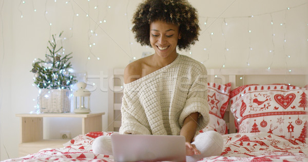 Happy woman in sweater on bed using computer Stock photo © dash