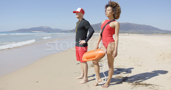 Female and male lifeguards posing on beach Stock photo © dash