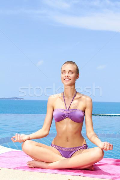Serene young woman sitting meditating Stock photo © dash