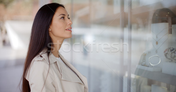 Thoughtful young woman eyeing shop merchandise Stock photo © dash