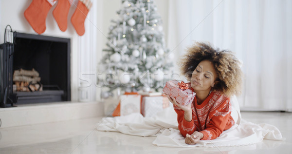 Young African girl lying looking at her Xmas gift Stock photo © dash