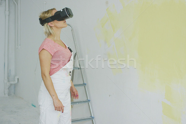 Stock photo: Female in overalls using virtual reality headset