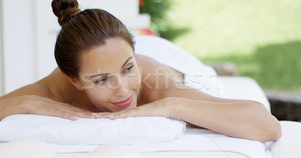 Woman on table with hair up in a bun smiles Stock photo © dash