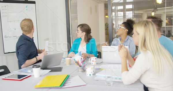 Young coworkers exploring graphic in office Stock photo © dash