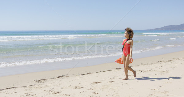 Lifeguard with rescue float walking along beach Stock photo © dash