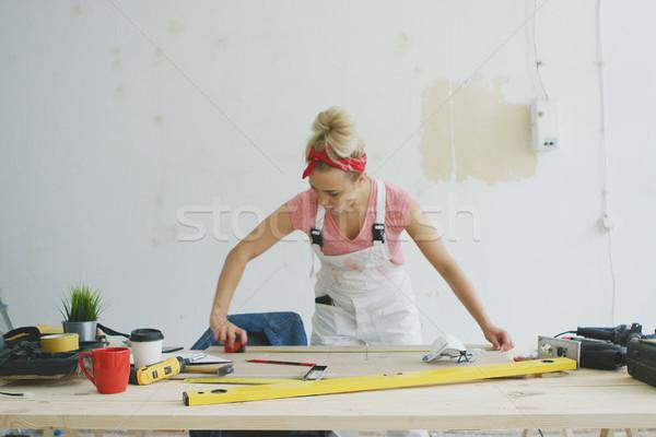 Female carpenter measuring wood on workbench  Stock photo © dash