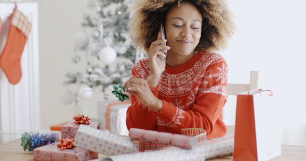 Woman chatting on a mobile as she wraps gifts Stock photo © dash