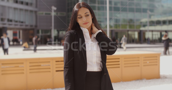 Stock photo: Smart young businesswoman rubbing her neck