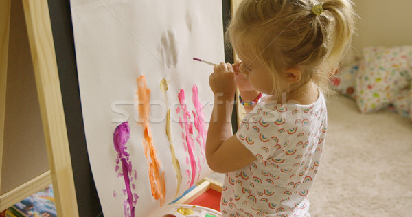 Little girl standing painting at an easel Stock photo © dash