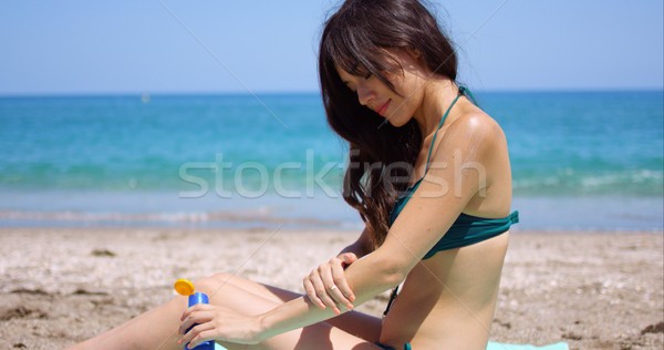Young woman applying sun cream to her legs Stock photo © dash