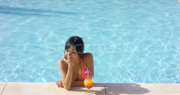 Contented woman at pool edge with drink Stock photo © dash