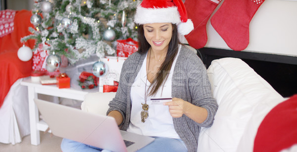 Happy young woman making online Xmas purchases Stock photo © dash