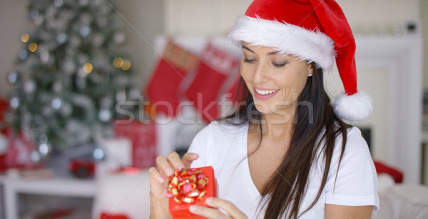 Smiling woman unwrapping her Christmas gift Stock photo © dash