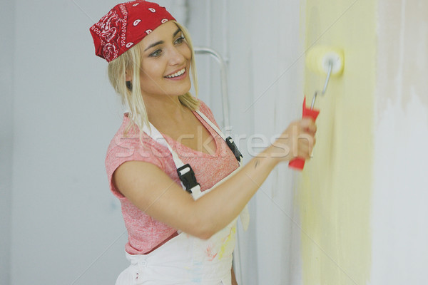 Smiling female painting wall with roller  Stock photo © dash