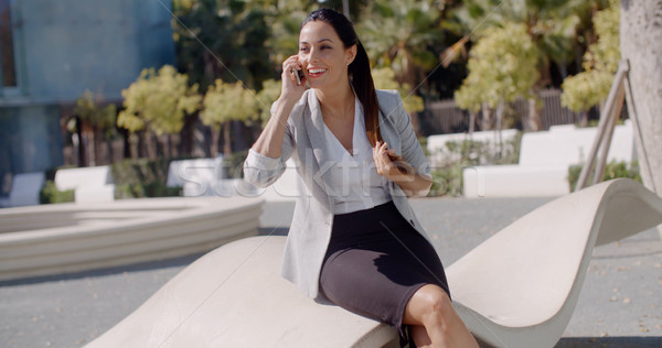 Attractive woman chatting on her mobile outdoors Stock photo © dash
