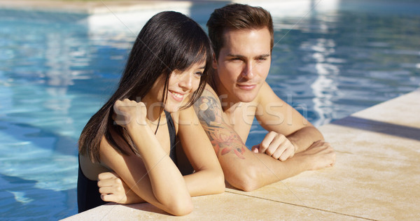 Diverse good looking couple stand in swimming pool Stock photo © dash