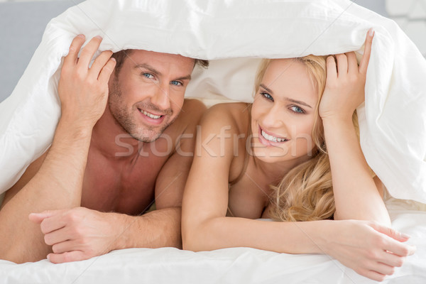 Young couple peeking out from under the bedclothes Stock photo © dash